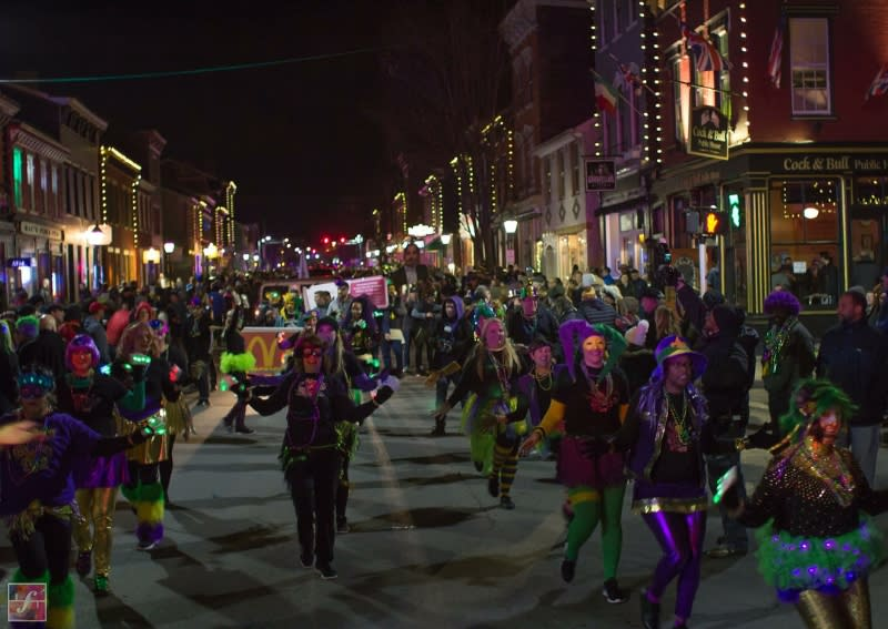 People dressed in green, purple and gold holding lights and marching in Mainstrasse Village's mardi gras parade at night.