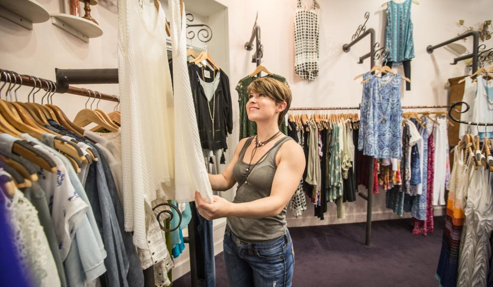 Young woman admiring a top in a clothing boutique.