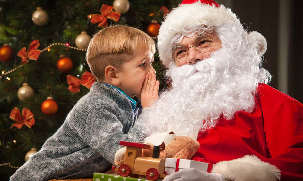 Photo of a boy whispering his gift request to Santa in front of the tree