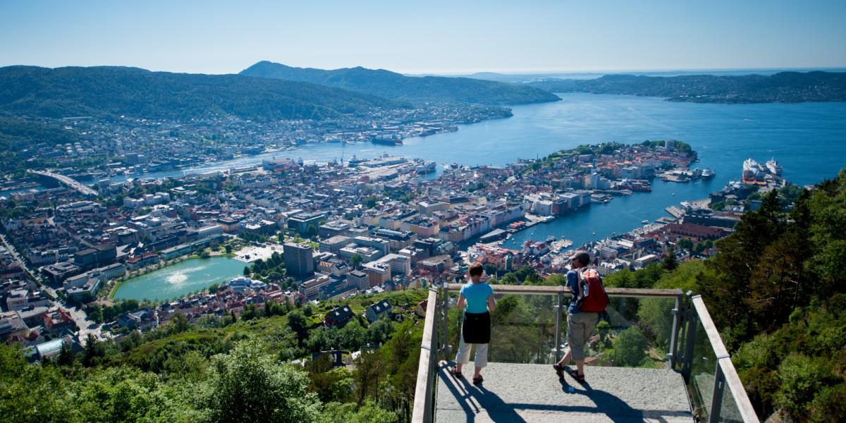 En mann og en dame nyter utsikten fra Fløyen i Bergen en sommerdag