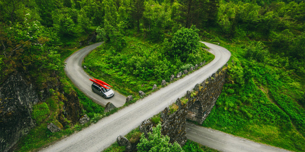 Road safety: A car with kayaks on the roof driving the ascending road loop Knuten in Geiranger, Fjord Norway