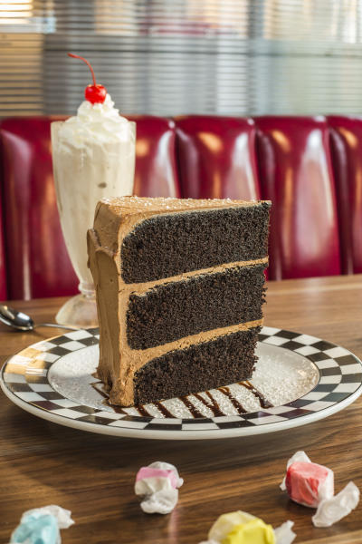 Giant piece of chocolate cake with a milkshake in an old school diner booth.