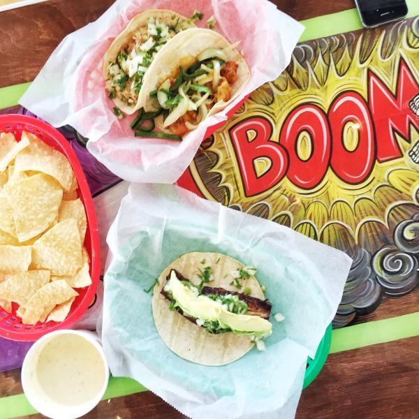 Table spread at Tacodeli including tacos, chips and coffee