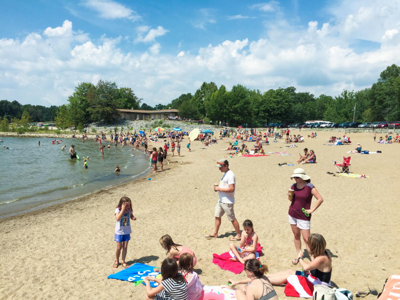People in the water and sunbathing at Monroe Lake
