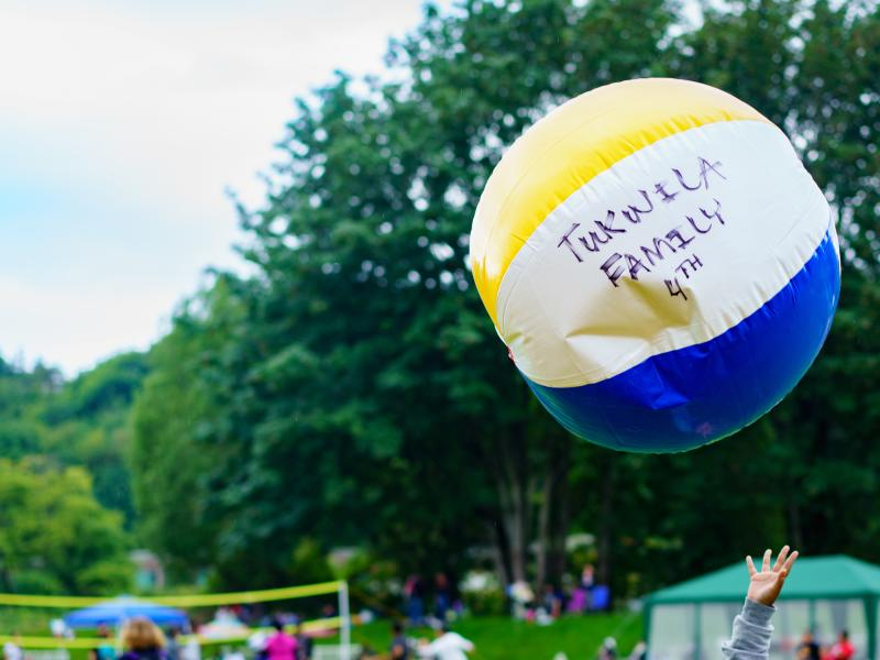 """beach ball with """"Tukwila Family 4th"""" written on it soaring above families at park"""