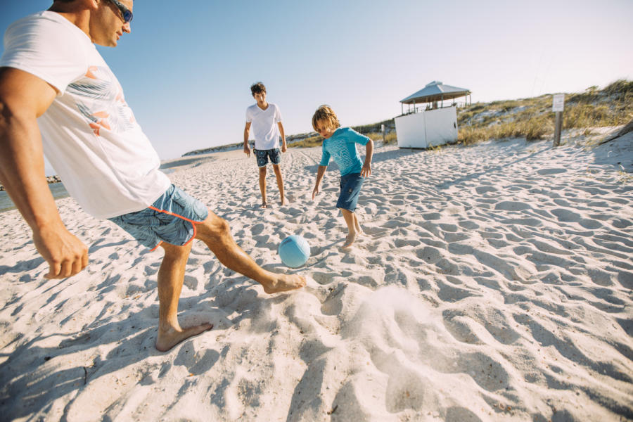 Family Beach playing soccer
