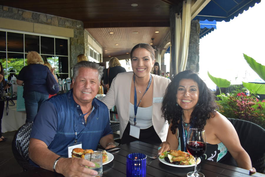 Three people smiling together at a networking event in Saratoga National