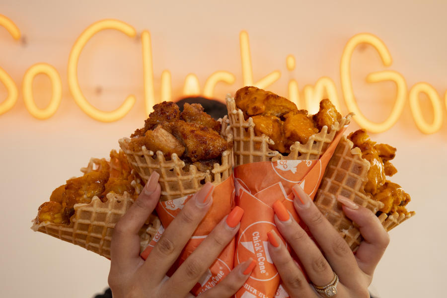 Person holding waffle cones with fried chicken from Chick 'n Cone in Fort Lauderdale