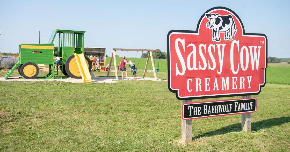 Sassy Cow Creamery sign in front of a playground designed like a tractor