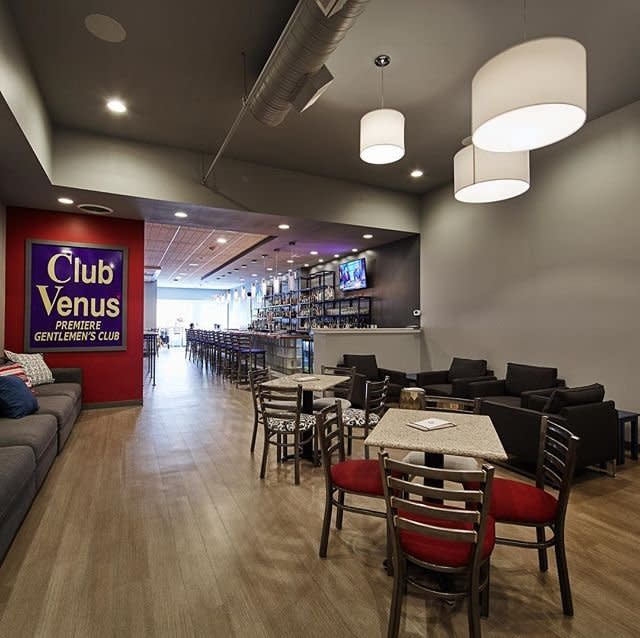 Inside The Globe Covington bar, with long modern bar, wood floors, red-seat chairs, and the old blue Club Venus sign on the wall