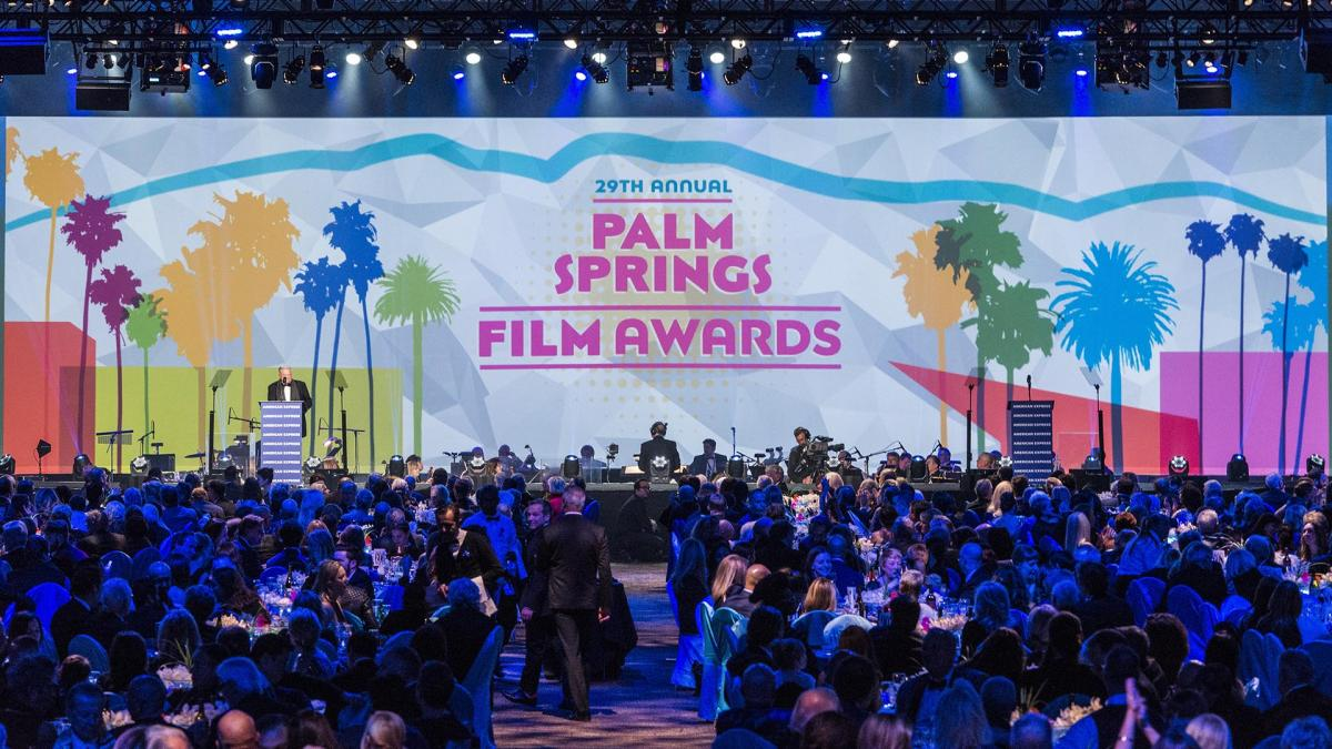 photo of gala attendees at the Palm Springs Film Fest looking at the stage and a presenter