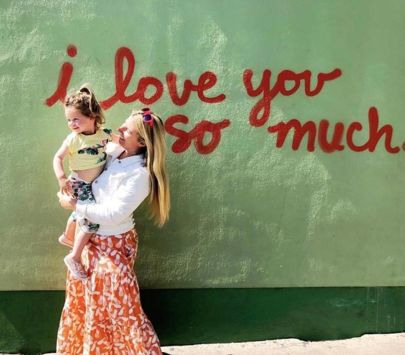 woman holding daughter in front of i love you so much mural at jos in austin texas