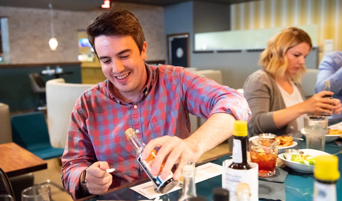 Main in plaid shirt gets ready to taste sample of bitters