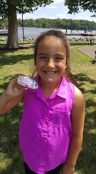 Child with purple painted rock in Bristol