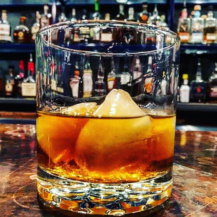 Closeup of bourbon cocktail in a clear glass with bourbon bottles in the background