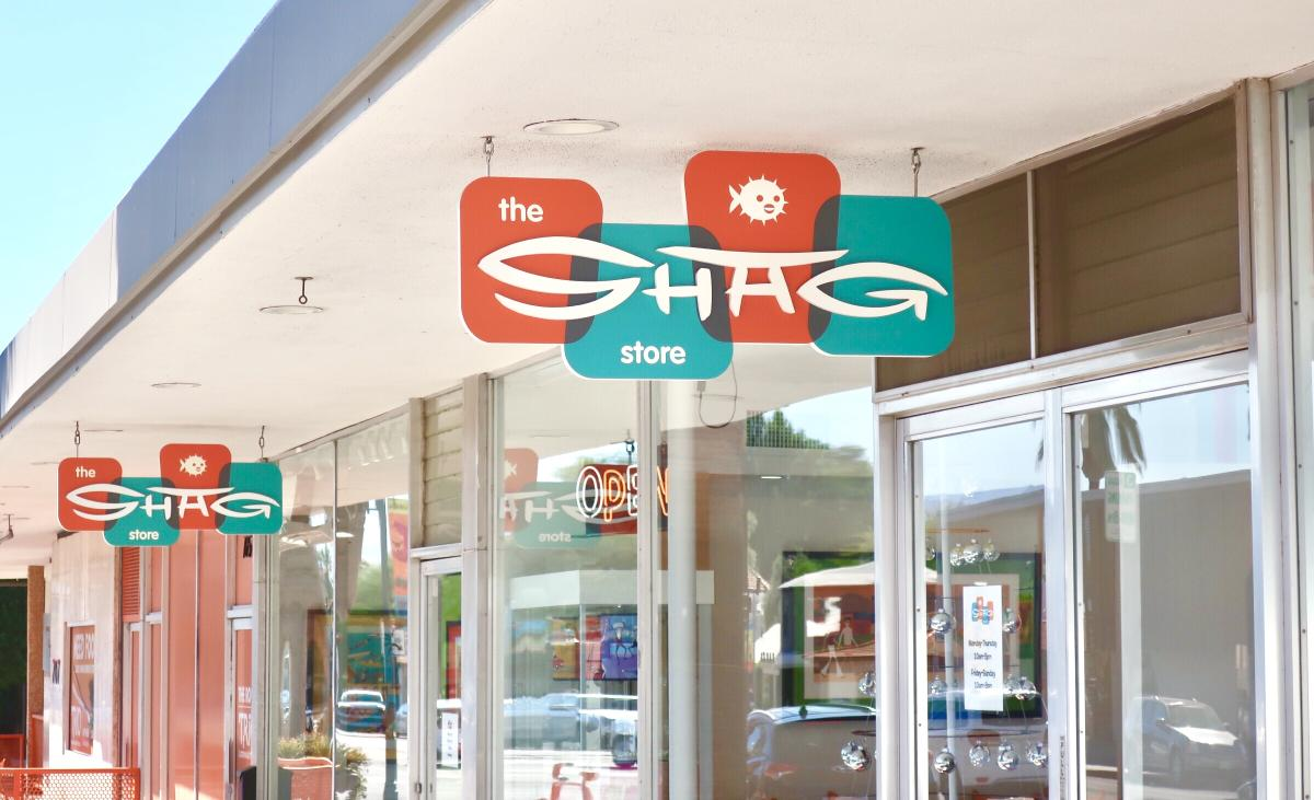 Orange and teal sign hanging outside of shop for SHAG Art Gallery