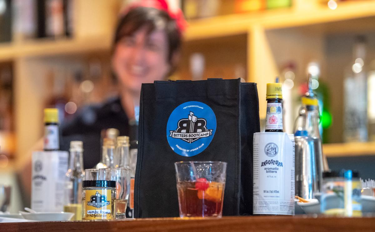 Old Fashioned cocktail in front of Bitters Boot Camp tote bag