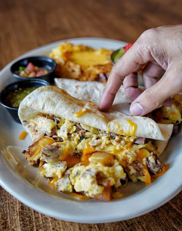 The Toasted Yolk's Brisket Tacos - Two flour tortillas filled with a heaping scoop of 12 hour smoked lean brisket, scrambled eggs, roasted potatoes, and cheddar cheese. Served with pico de gallo and salsa verde.
