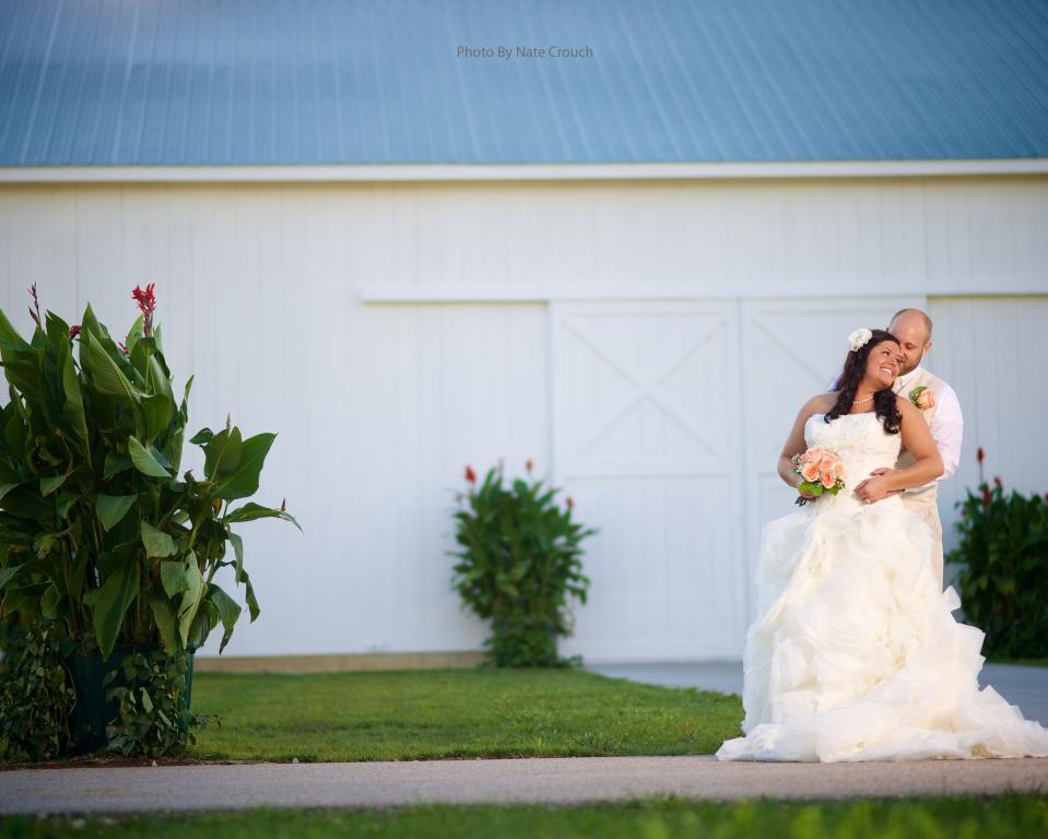 Couple in front of barn with flowers - Nate Crouch