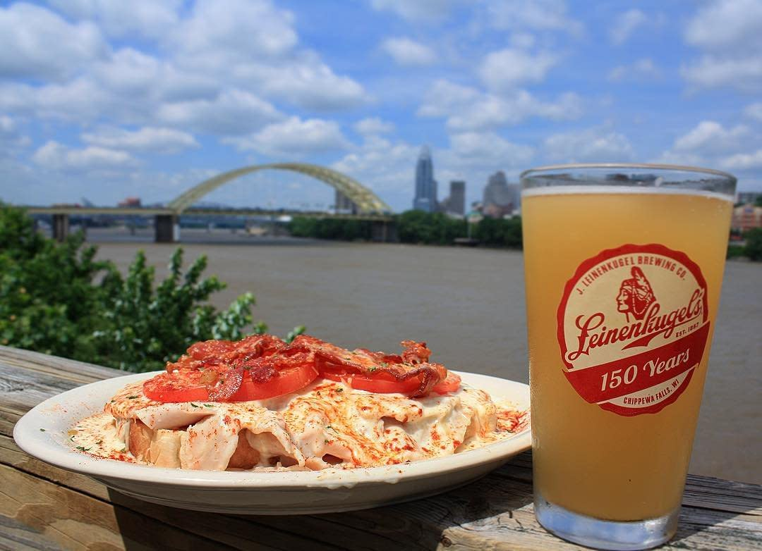Plate of food and a beer in foreground on deck rail of Buckhead restaurant with view of Cincinnati