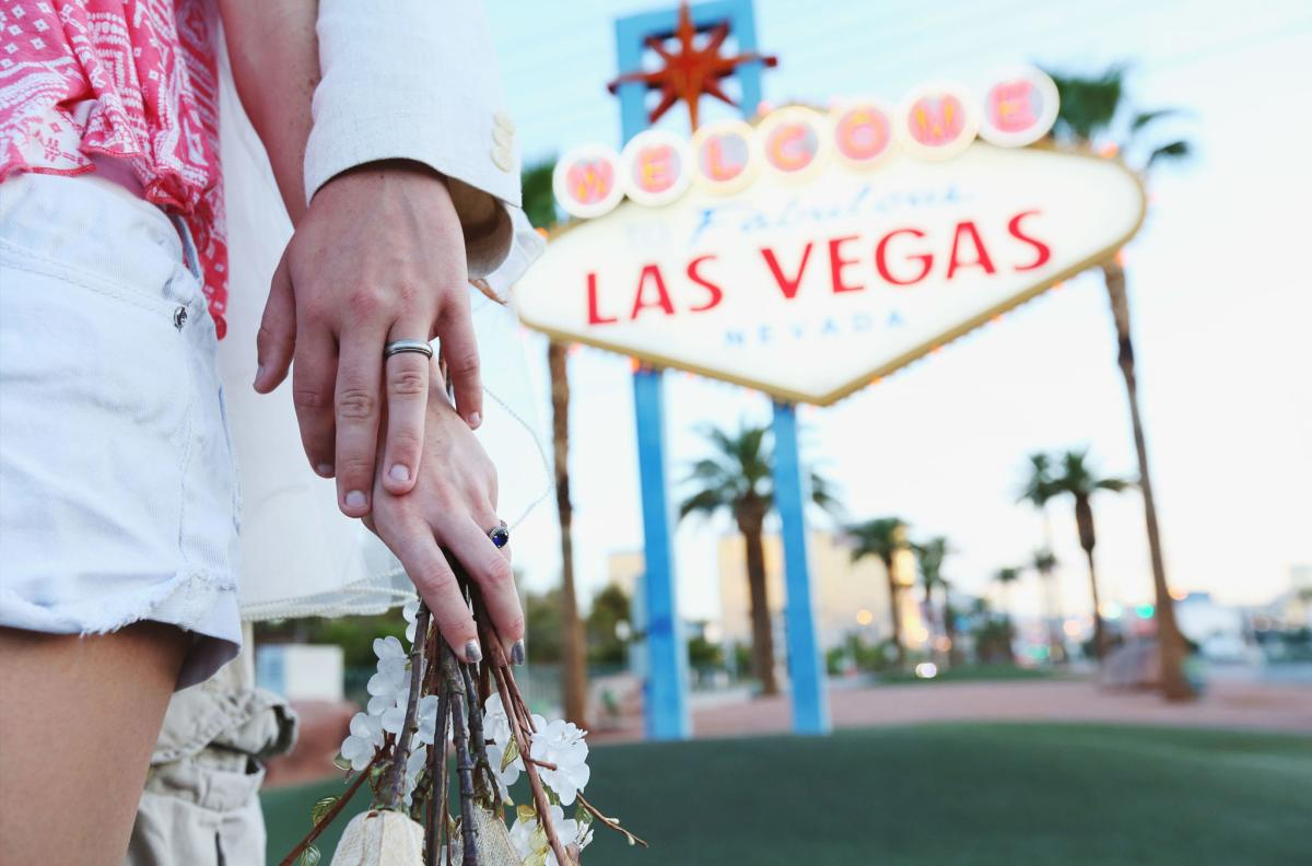 Married Couple Holding Hands in Front of the Las Vegas Sign