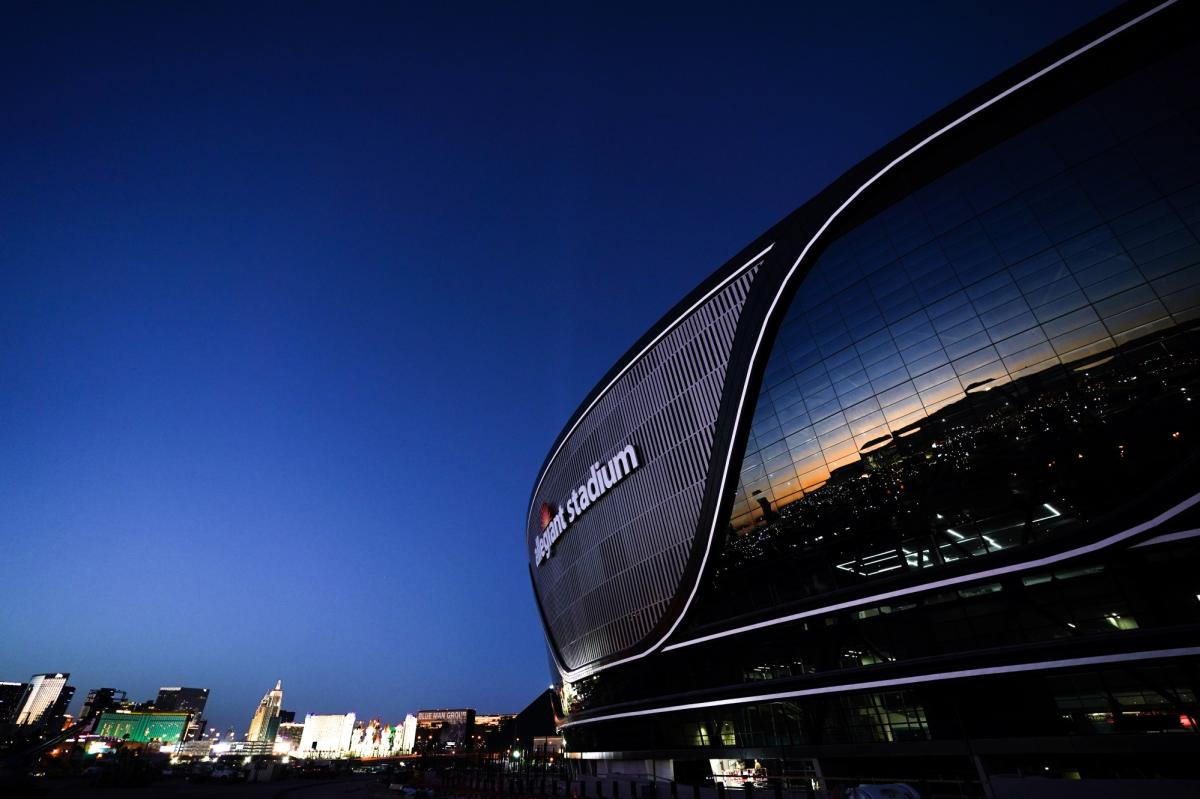The sunset and bright lights reflect off the exterior of the Allegiant Stadium in Las Vegas.