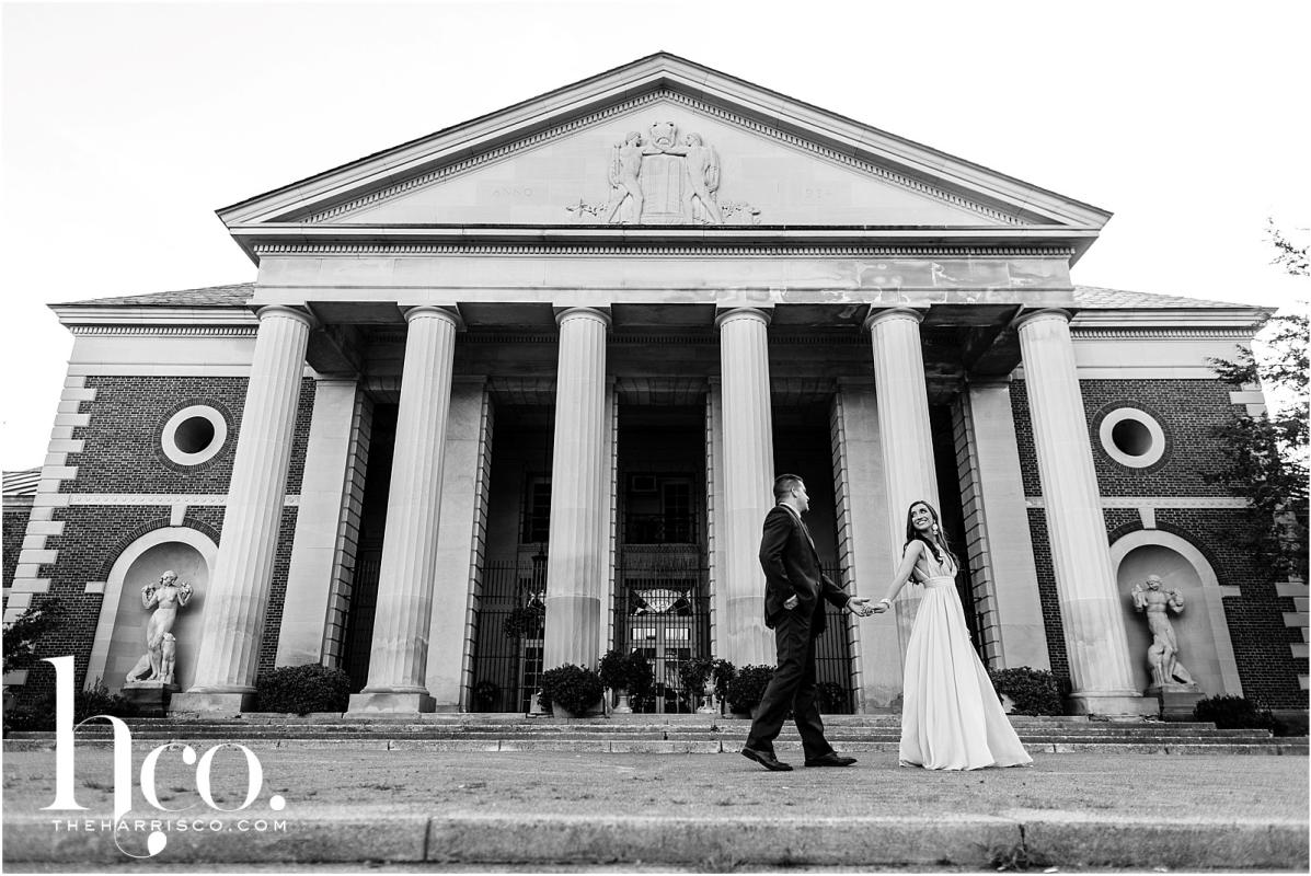 Black and white shot of couple holding hands outside of Hall of Springs in Saratoga NY