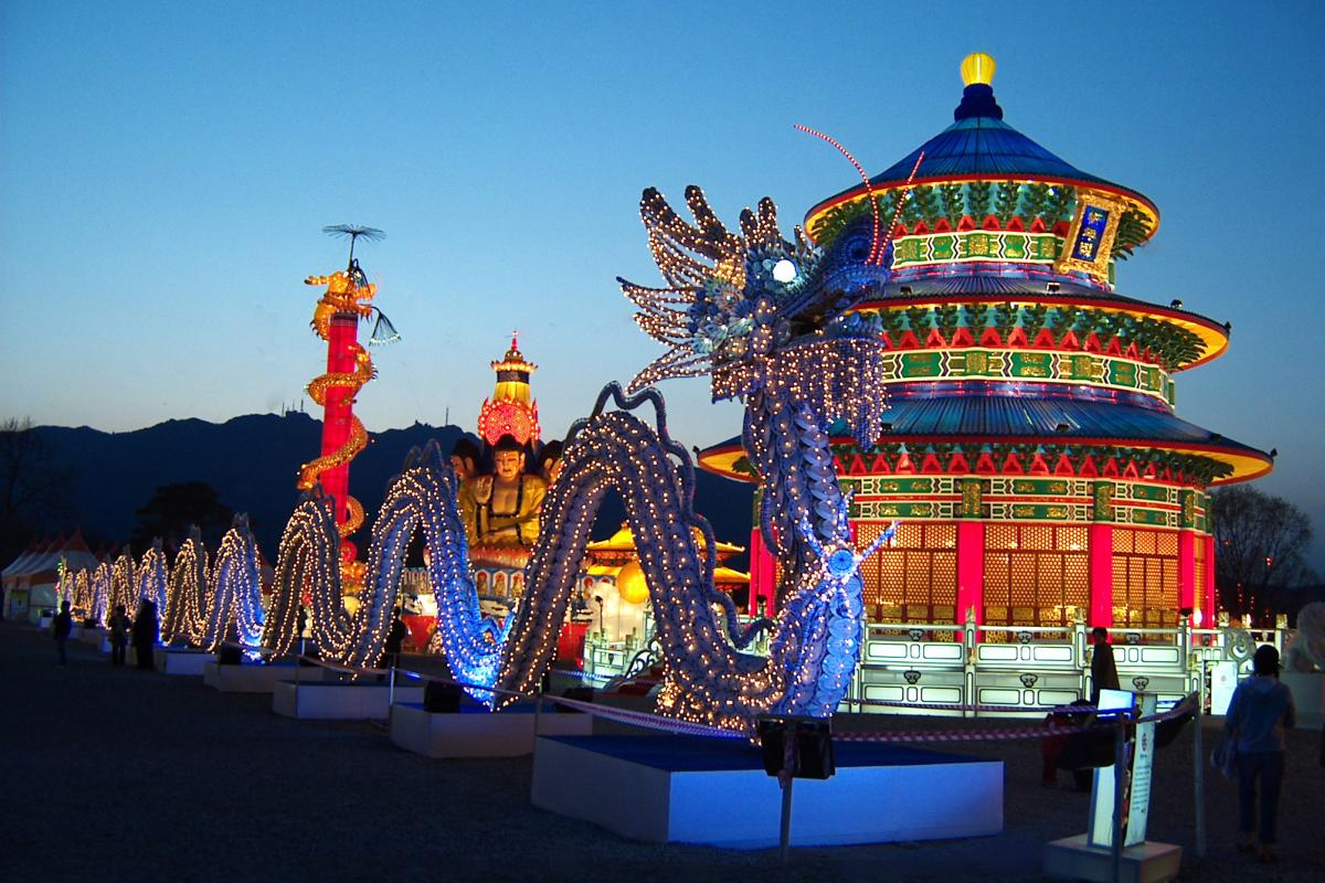 Giant dragon in front of a lit temple at the Lights of the North festival