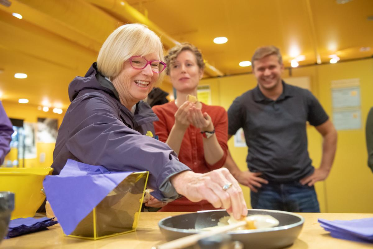 Woman dips cracker in mustard mixture during a tasting