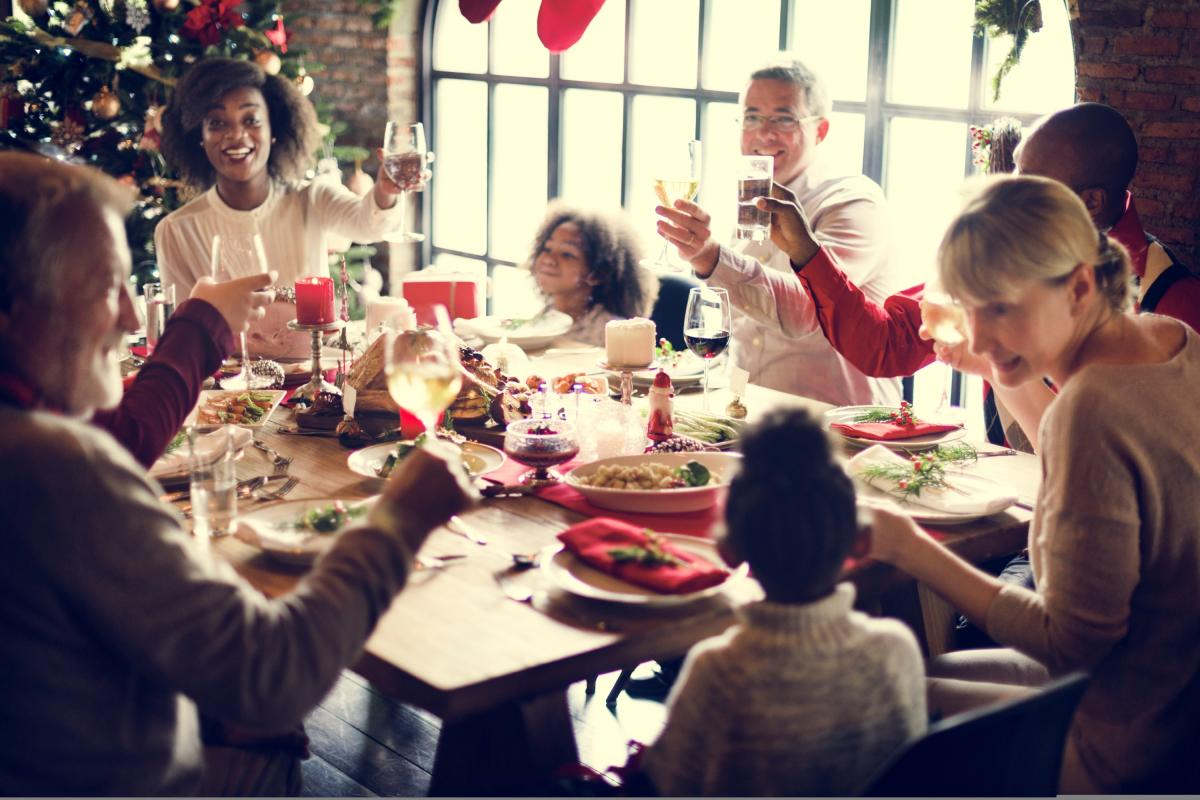 An extended, mixed family cheersing around a festive table