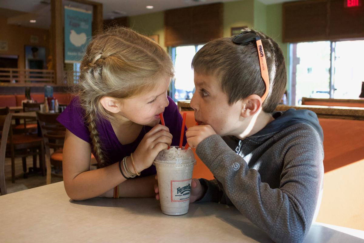 Children sharing a milkshake at Farmer Boys in Irvine