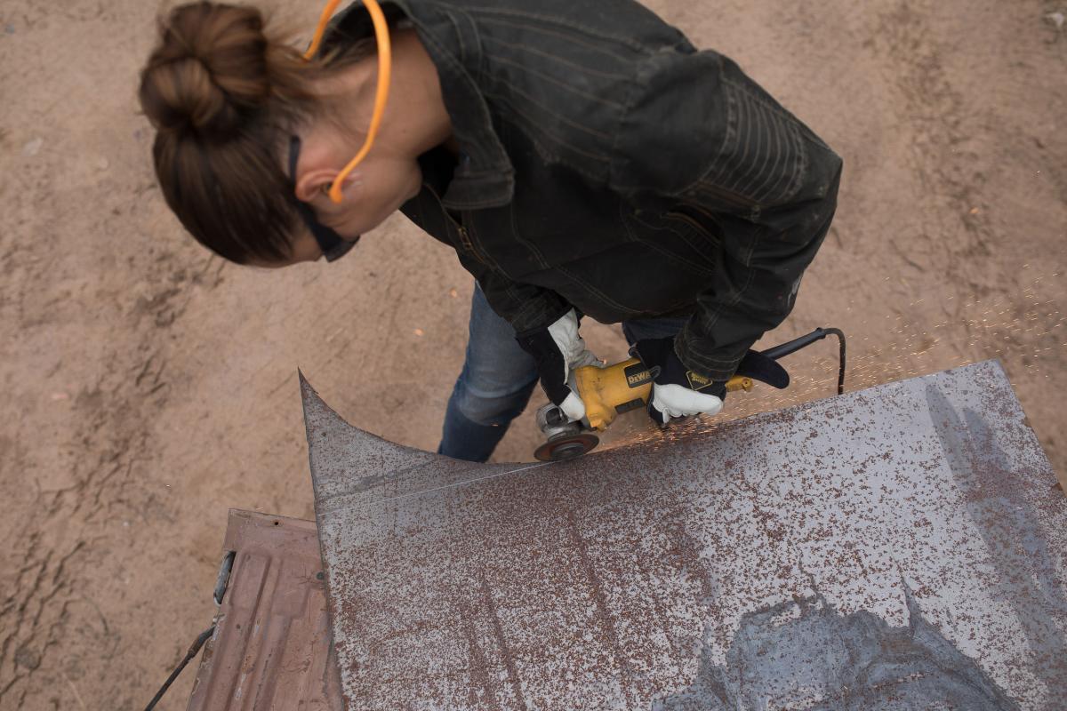 Artist Rose Simpson cutting sheet metal