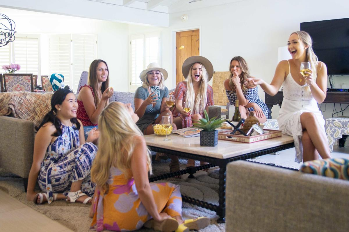 Seven women gathering in a living room laughing and drinking wine.