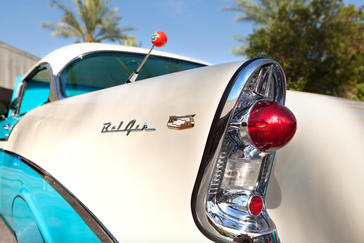 White and baby blue classic car with red tail lights.