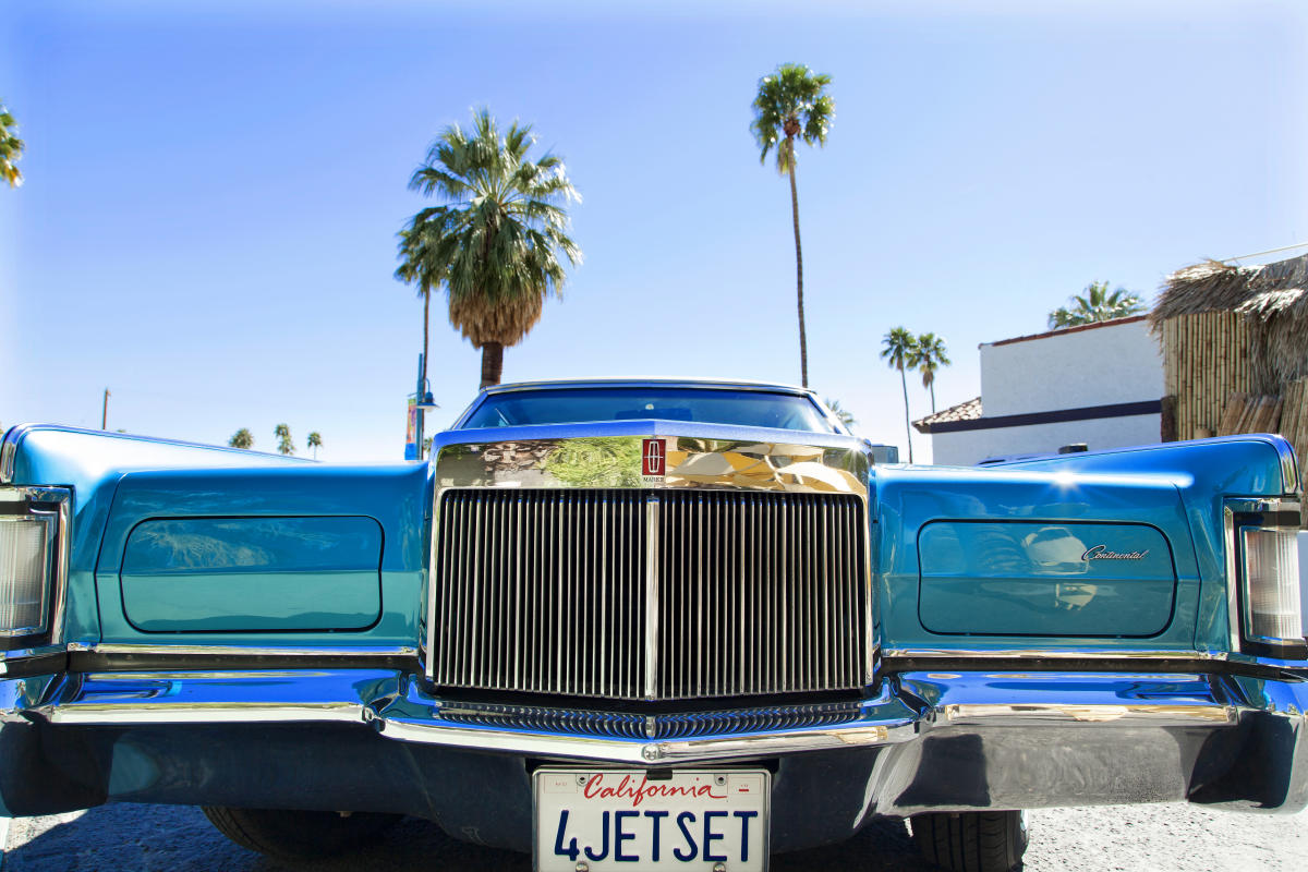 Powder blue classic Cadillac with palm trees in the background.