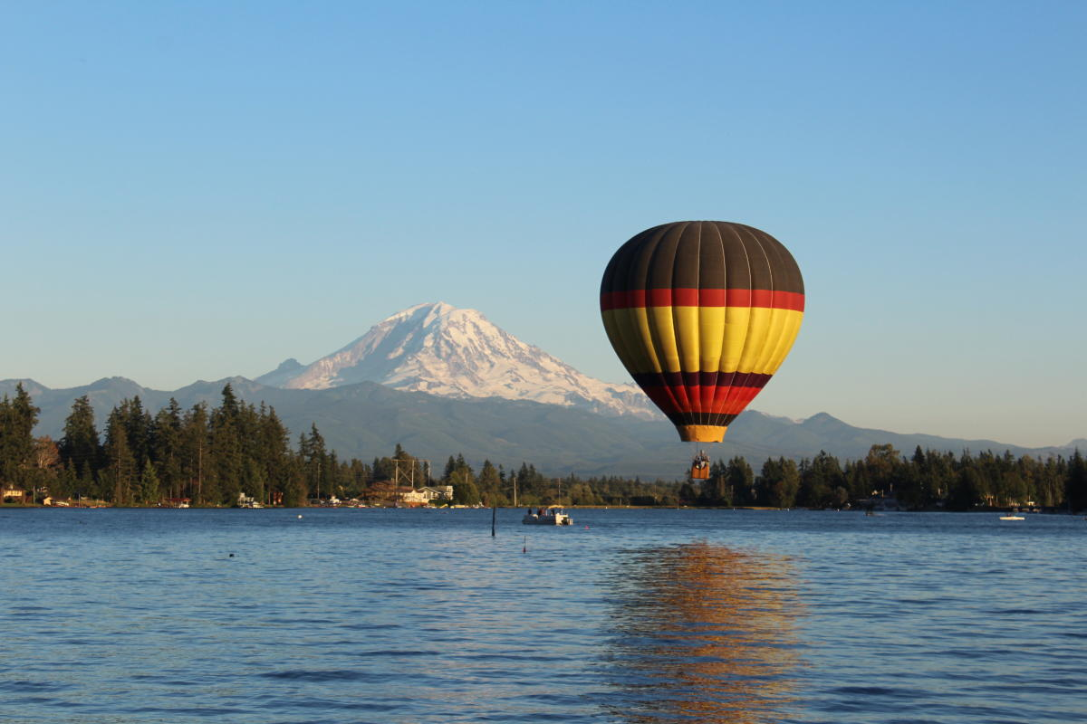 Hot Air Balloon over water in front of snowy mountain