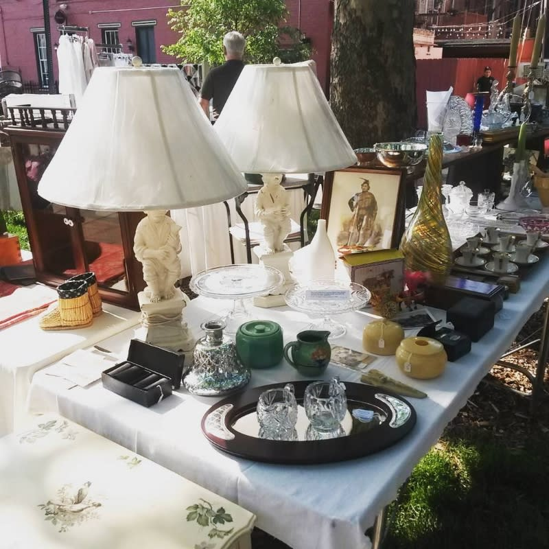 Long table with white cloth outside at Mainstrasse Village, covered in lamps, ceramics and collectibles