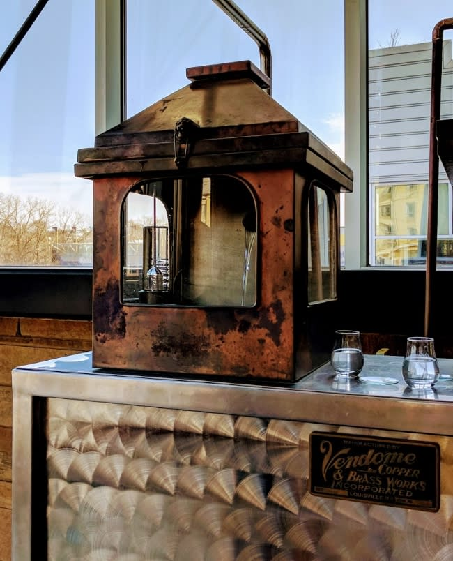 Copper spirit safe with new make bourbon visible through the glass window at New Riff Distillery
