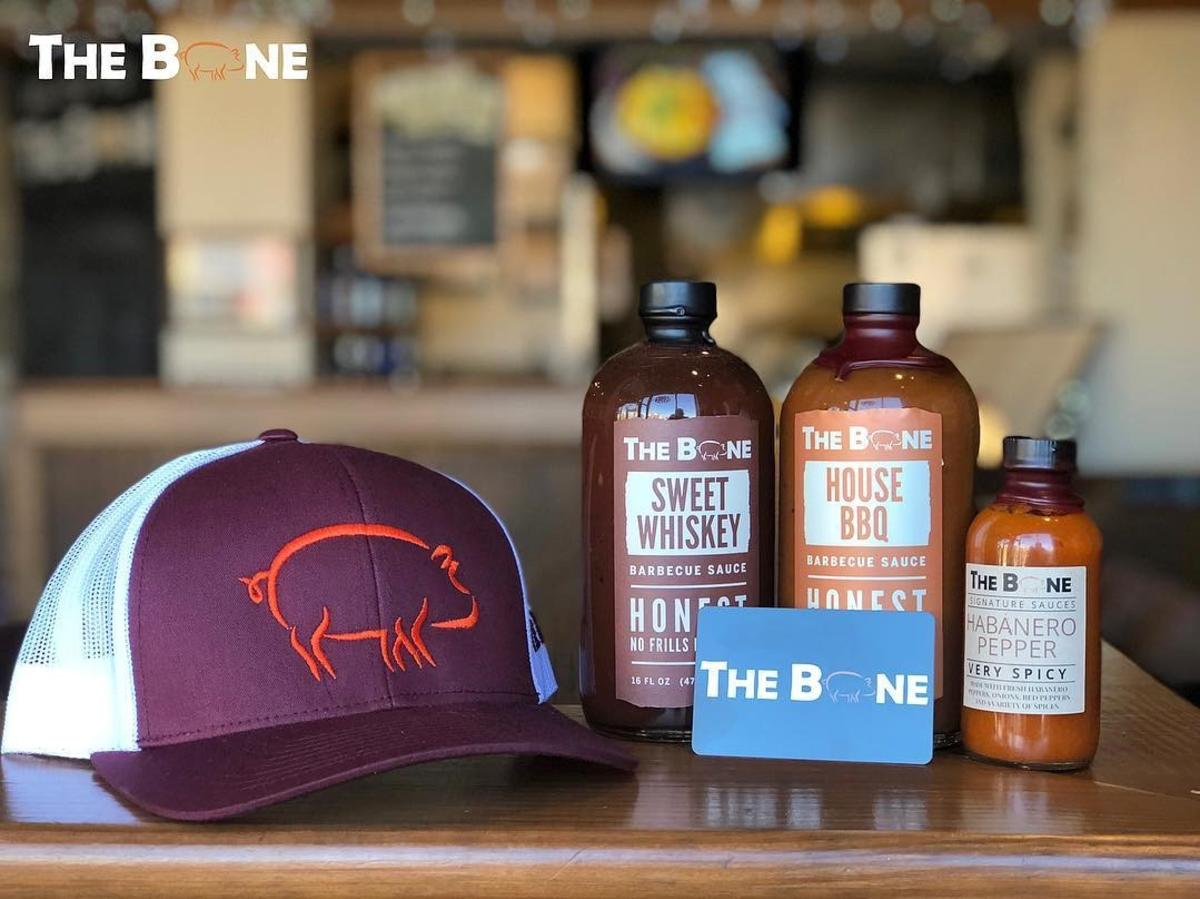 The Bone BBQ hat, BBQ sauce and gift card on a table