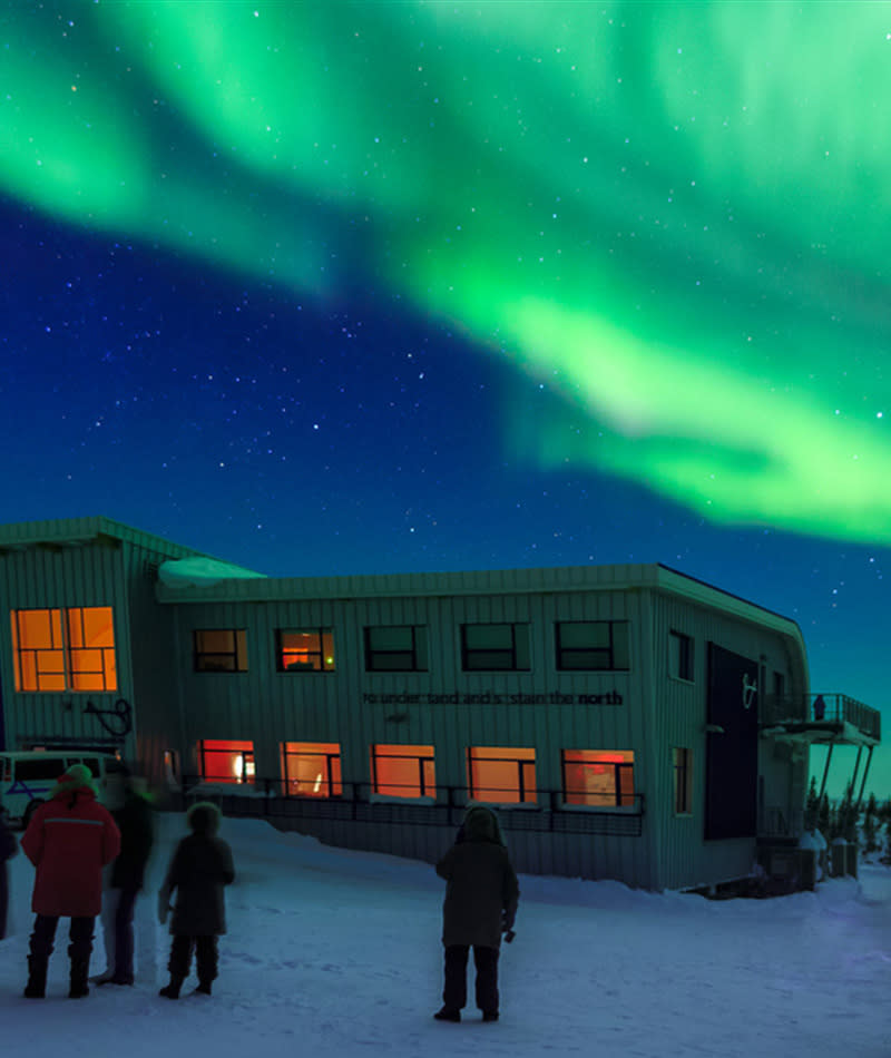 People stand outside of the Churchill Northern Studies Centre under the Northern Lights