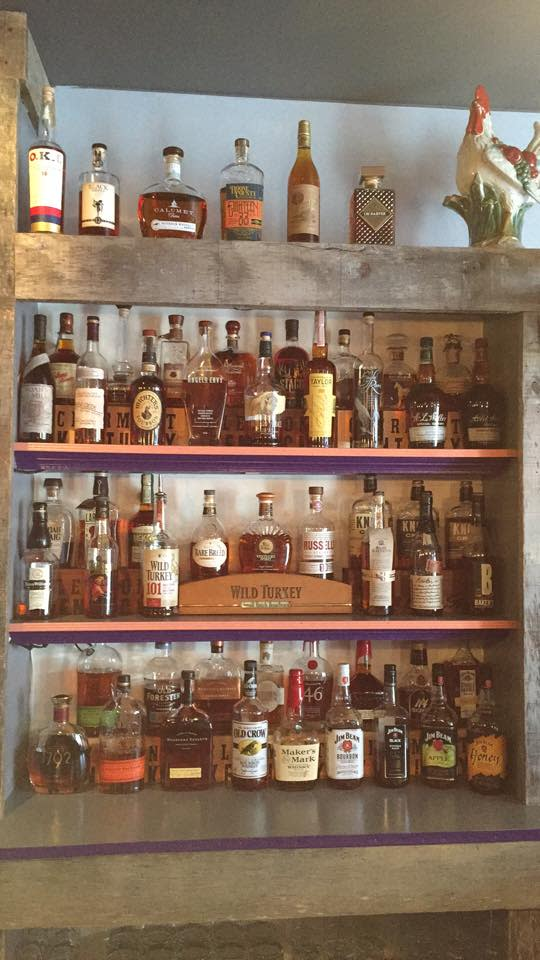 Four shelves of bourbon at the purple poulet restaurant