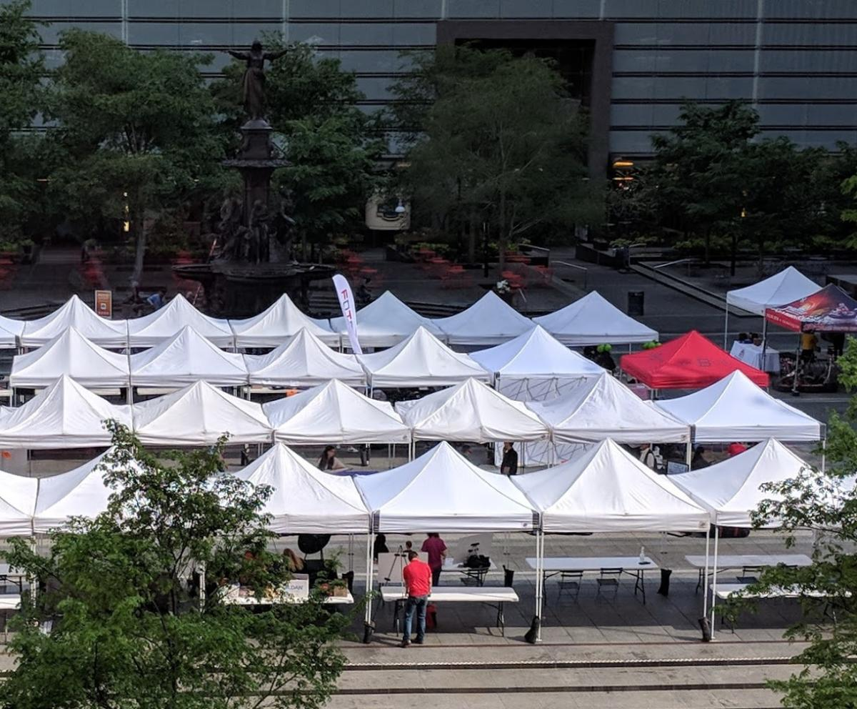 "Rows of white tents on Fountain Square in Cincinnati with one red tent that reads ""The B-Line"" in blue lettering"
