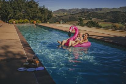 Couple in swimming pool on a inflatable flamingo