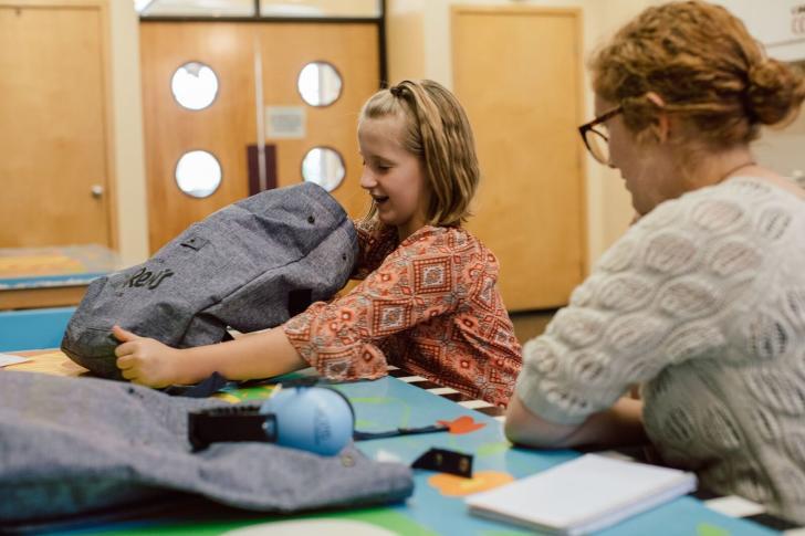 Family opening the Grand Rapids Children's Museum Sensory Friendly Tool Kit bag