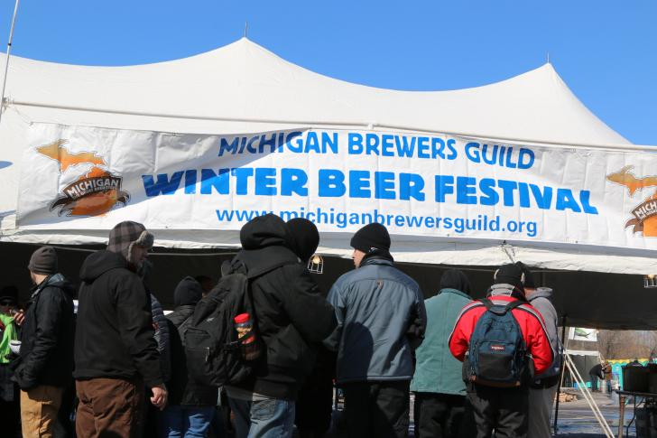 People lining up under tent for the Winter Beer Festival in Grand Rapids