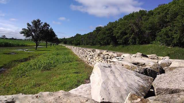 Limestone retaining wall along a curved road with a field, trees and blue skies.
