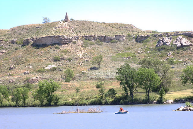 A small canoe sits in the lake that is at the base of a rocky hillside