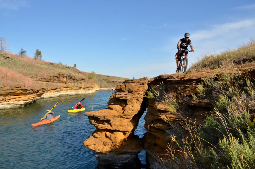 Man biking on a trail above two kayakers