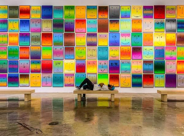 A man laying on a bench in front of the Happy Exhibit at NSU Art Museum