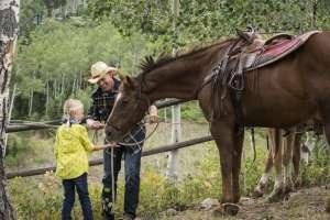 Girl Prepares to Ride a Horse